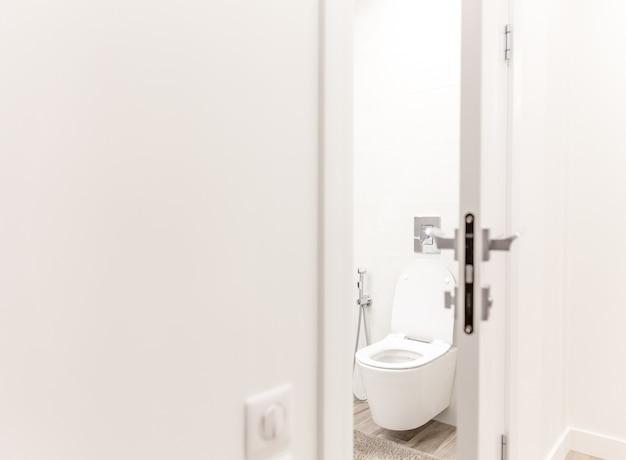 Porta aberta no banheiro com vaso sanitário