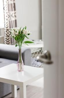 Porta aberta para o quarto com buquê de flores na mesa, interior escandinavo
