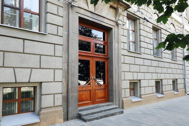 Porta alta da frente de um prédio de concreto com janelas da calçada da cidade