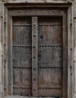 Porta antiga esculpida com gravuras de uma antiga casa de barro em omã