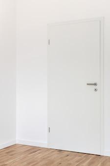 Porta branca fechada com maçaneta cromada cinza e buraco de fechadura com chave contra uma parede branca na sala