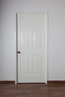 Porta branca fechada na parede cinza