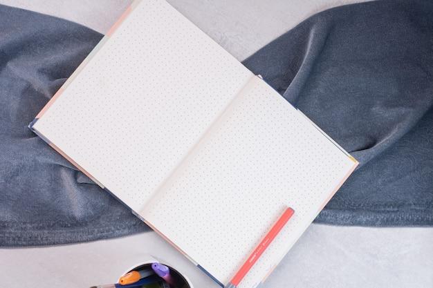 Porta-canetas e caderno aberto na superfície branca