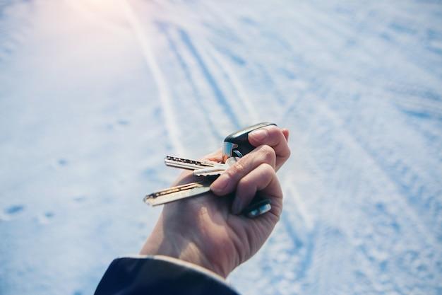Porta-chaves com as chaves do carro na mão sobre neve. tentando ligar um carro no inverno