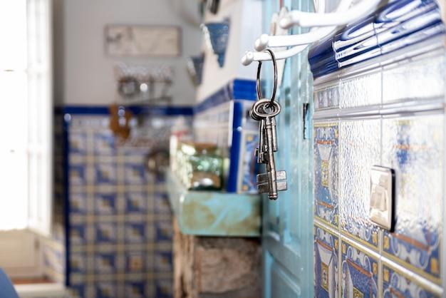 Porta-chaves com chaves antigas pendurado em um fogão de cerâmica antigo.
