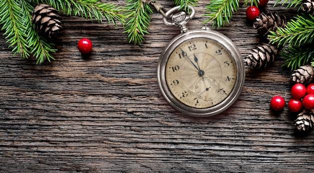 Porta-chaves de bolso de ano novo velho assistir véspera à meia-noite com ramos de pinheiro, cones e decorações na mesa de madeira envelhecida rústica. copie o espaço