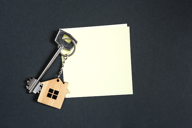 Porta-chaves em forma de casa com chave sobre fundo preto com lençol quadrado para apontamentos.