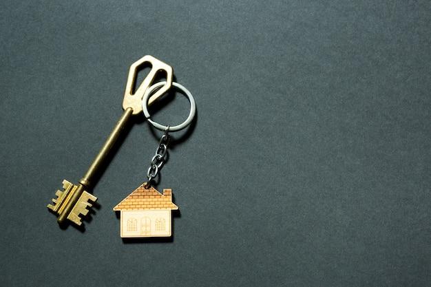 Porta-chaves em forma de casa com chave sobre fundo preto. construção, desenho, projeto, mudança para nova casa, hipoteca, depósito, aluguel e compra de bens imóveis. copie o espaço