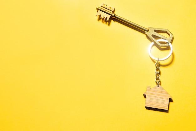 Porta-chaves em forma de casa de madeira com chave sobre fundo amarelo. construção, desenho, projeto, mudança para nova casa, hipoteca, aluguel e compra de bens imóveis. copie o espaço