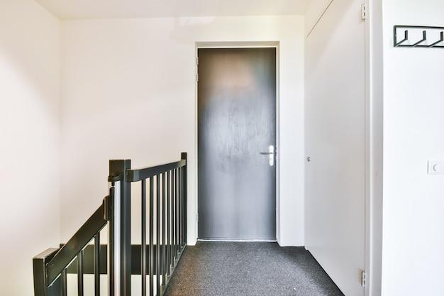 Porta cinza fechada do quarto localizada no topo da escada em uma casa moderna