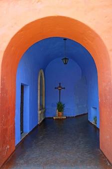 Porta colorida alaranjada brilhante que conduz à capela azul vívida