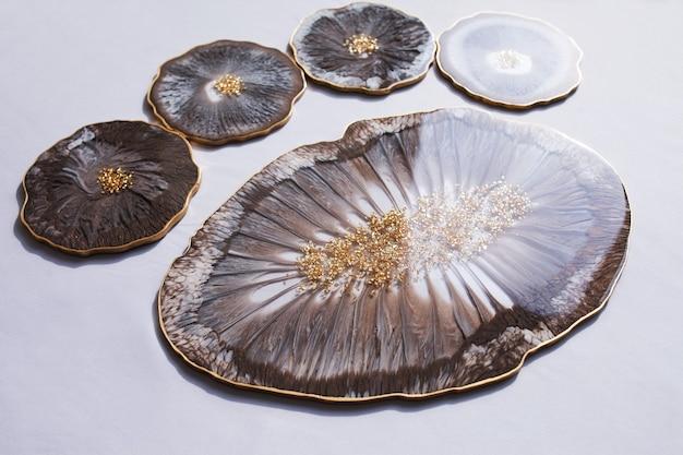 Porta-copos, bandeja de resina epóxi, pedra marinha recortada em fundo cinza.