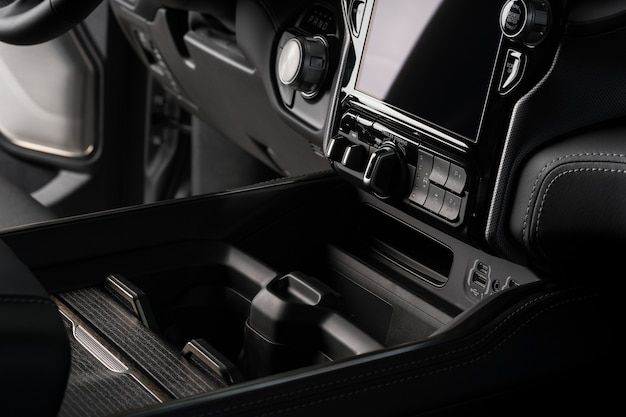 Porta-copos close-up dentro de um carro luxuoso preto, tela de sistema de tela sensível ao toque