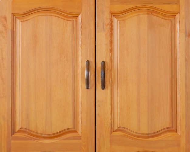 Porta de armário de madeira amarela com puxadores marrons