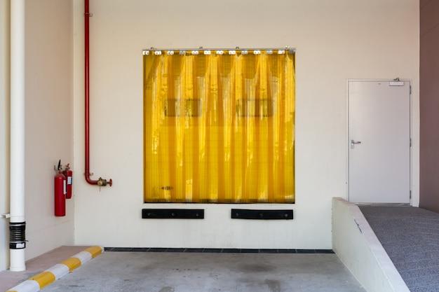 Porta de entrada da indústria com cortina de tira de plástico amarelo transparente.