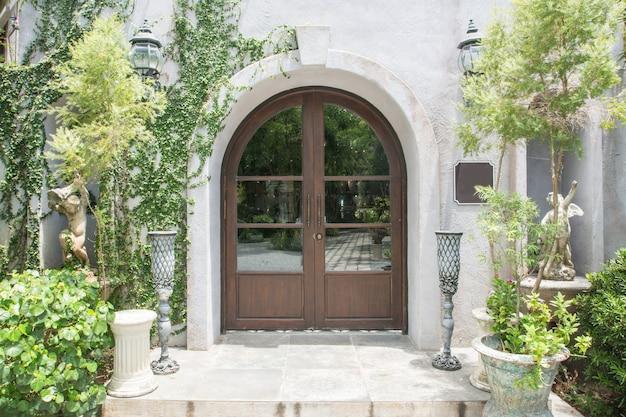 Porta de entrada de madeira elegante cercada por jardim