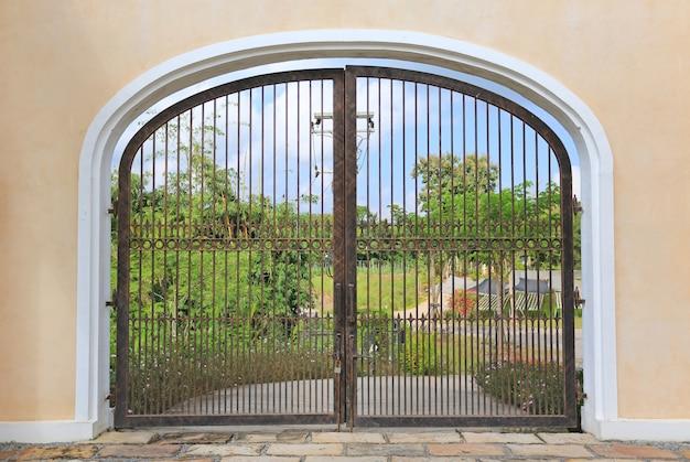 Porta de ferro na parede de cimento para o jardim.