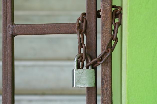 Porta de ferro velho tem ferrugem, trancada com uma sala de exposições. com um cadeado que não pode ser aberto