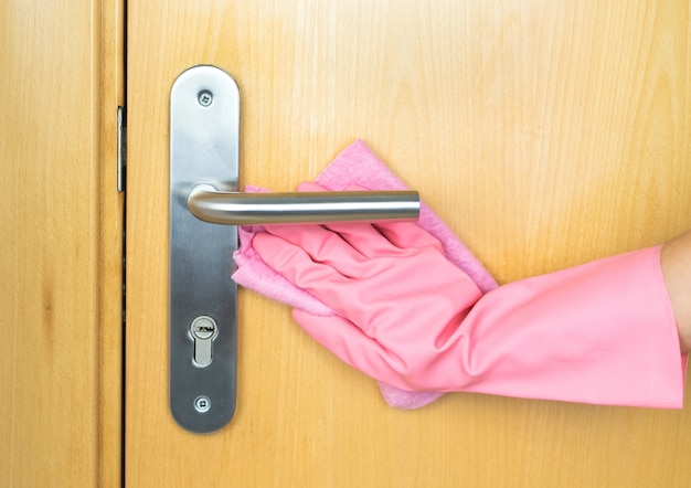 Porta de limpeza de mão com luvas rosa. conceito covid-19. copie o espaço.
