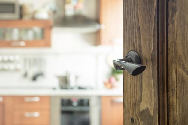 Porta de madeira aberta à cozinha moderna.