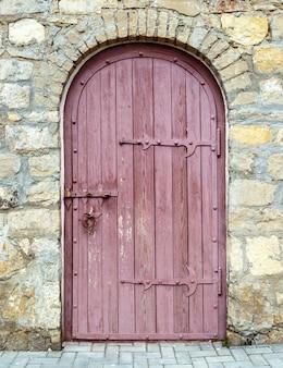 Porta de madeira antiga com fechadura na parede de pedra