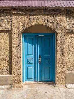 Porta de madeira azul vintage em uma autêntica vila de montanha.