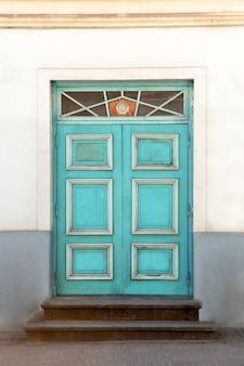 Porta de madeira com elementos de decoração em fachada de edifício antigo. tallinn, estônia. porta antiga de madeira colorida