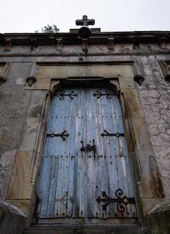 Porta de madeira da igreja do grunge azul na parede de tijolo.