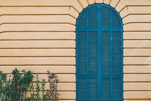 Porta de madeira em arco azul em uma parede amarela
