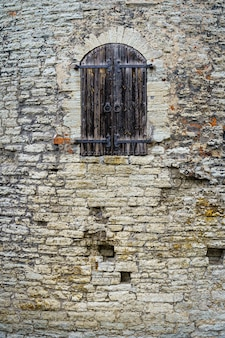Porta de madeira medieval na fachada do castelo de pedra.