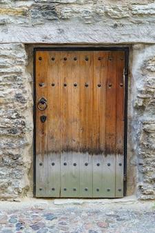 Porta de madeira muito antiga com fechadura e ferragens de metal.