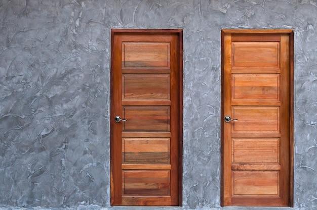 Porta de madeira na textura da parede de concreto