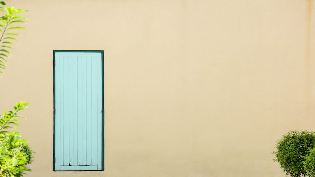 Porta de madeira velha azul no edifício de concreto laranja pálido