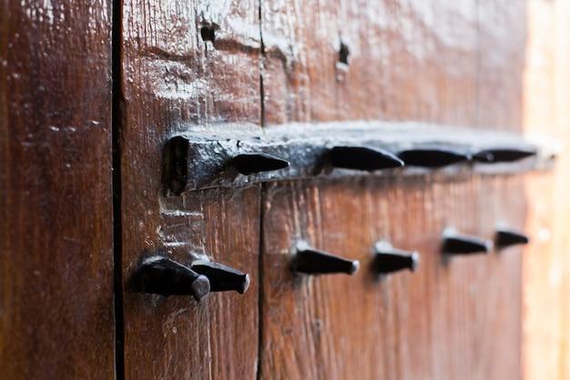 Porta de madeira velha com espinhos de metal