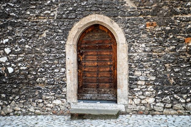 Porta de madeira velha com parede de pedra na rua antiga