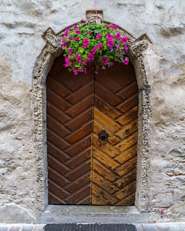 Porta de madeira velha em edifício medieval com vaso de flores.