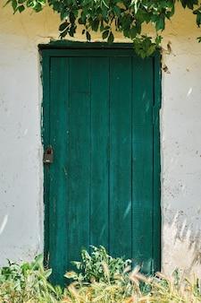 Porta de madeira verde velha em uma parede de pedra de uma casa ou celeiro, ramos de hera emolduram uma abertura, campo. decoração de interiores ou plano de fundo, moldura vertical com espaço de cópia