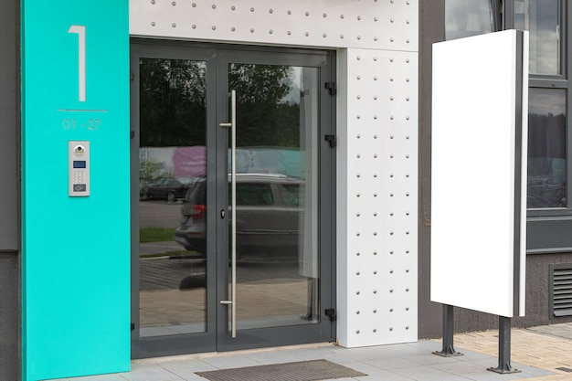 Porta de vidro de acesso ao prédio com banner de propaganda em branco perto dele