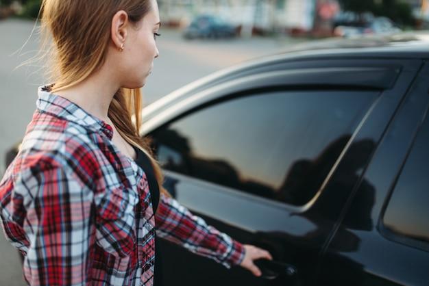 Porta do carro aberta de mão feminina, conceito de motorista iniciante