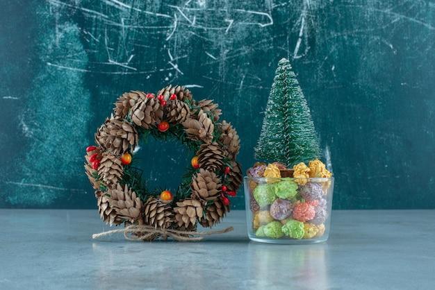 Porta-doces com nogulos e uma estatueta de árvore ao lado de uma coroa de pinha sobre mármore.