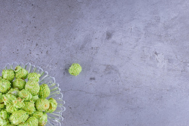 Porta-doces contendo uma pilha de pipoca verde com sabor sobre fundo de mármore. foto de alta qualidade