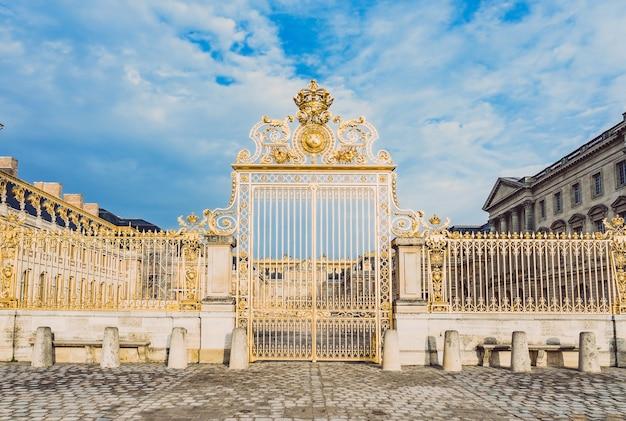 Porta dourada principal na fachada exterior do palácio de versalhes, paris, frança