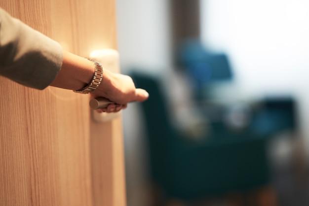 Porta entreaberta de um quarto de hotel com a mão