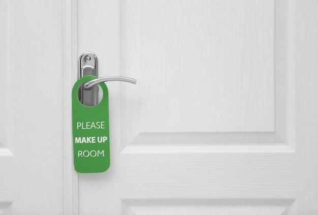 Porta fechada com placa please make up room na maçaneta do hotel