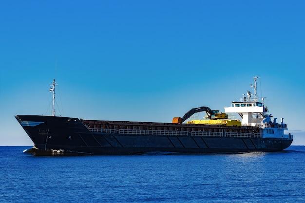 Porta-granel à vela preta. navio de carga com escavadeira de longo alcance movendo-se em águas paradas em dia de sol à beira-mar