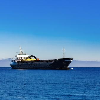 Porta-granel à vela preta. navio de carga com escavadeira de longo alcance se movendo em águas paradas em dia de sol à beira-mar