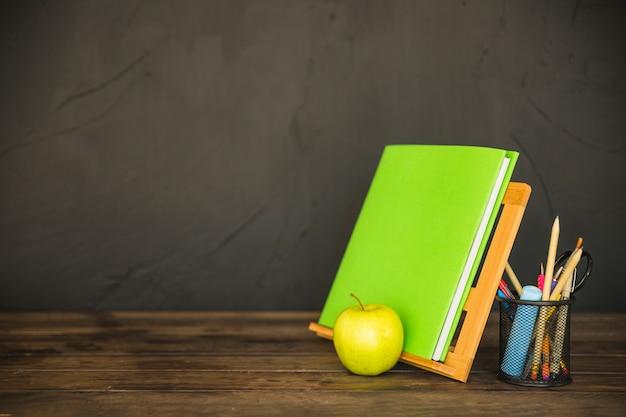 Porta-livros com papelaria e maçã