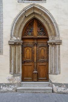 Porta muito antiga em arco de pedra de estilo medieval.