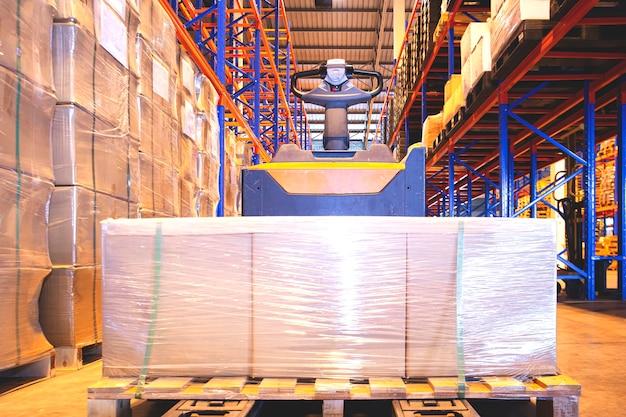 Porta-paletes de empilhadeira elétrica com caixas de embalagem no armazém de armazenamento transporte logística do armazém