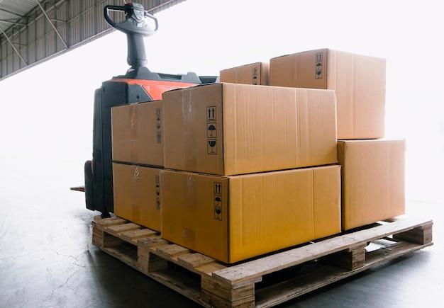 Porta-paletes de empilhadeira elétrica com caixas de pacotes na logística de armazém de armadores de paletes